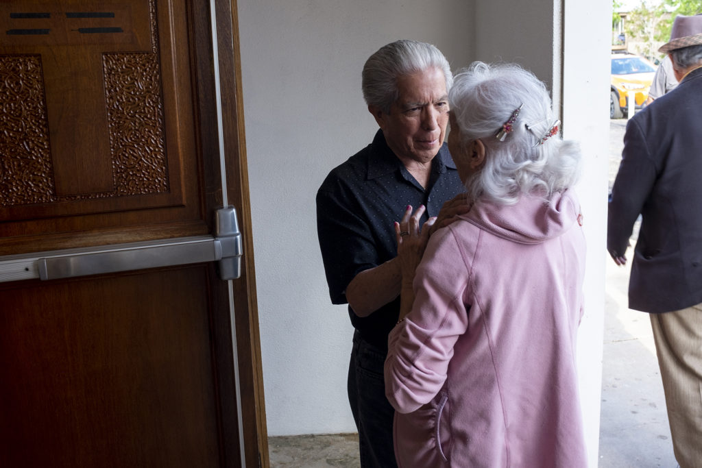 Lloyd Quintana greets a parishoner of Our Lady of Visitation church before its second of two masses for the year, May 31, 2019. (Kevin J. Beaty/Denverite)