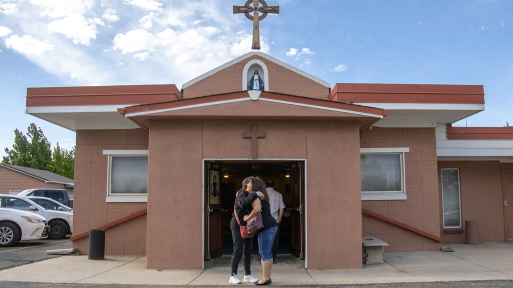 Parishioners embrace before Our Lady of Visitation holds its second of two masses for the year, May 31, 2019. (Kevin J. Beaty/Denverite)