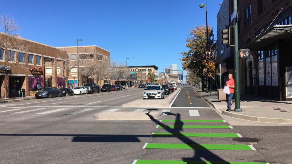 A rendering of the Broadway bike lane with a concrete curb and parked cars protecting bicyclists from traffic. (Courtesy, Kimley-Horn)