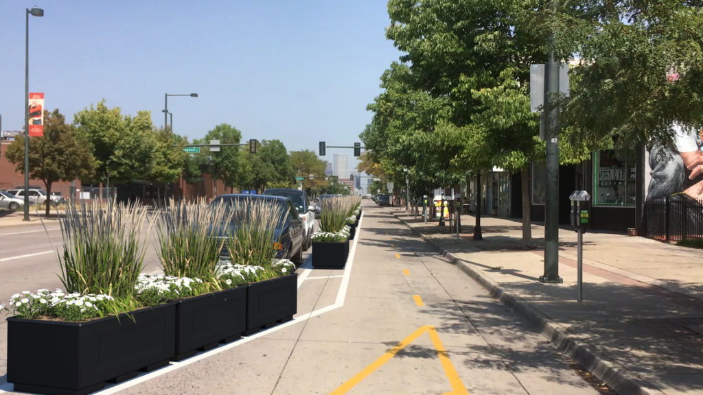 A rendering of the Broadway bike lane with planters and parked cars protecting bicyclists from traffic. (Courtesy, Kimley-Horn)