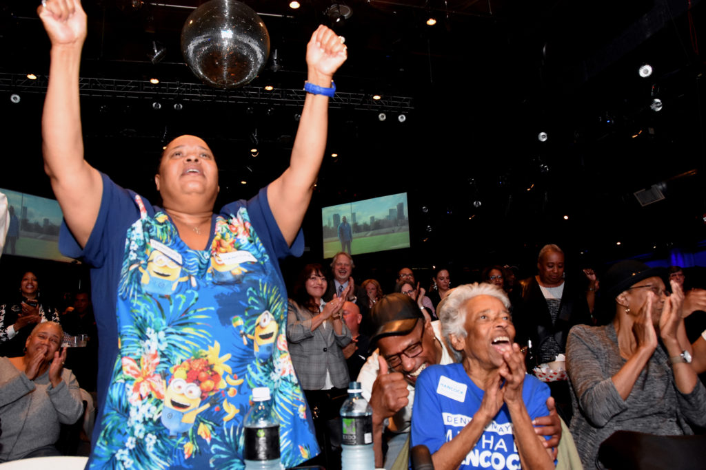 The mayor's sister Cheryl Gray (left), brother Darryl Hancock (middle with thumb up), and mother Scharlyne Hancock (right) celebrate during the mayor's election watch party. (Corey Jones/CPR News)