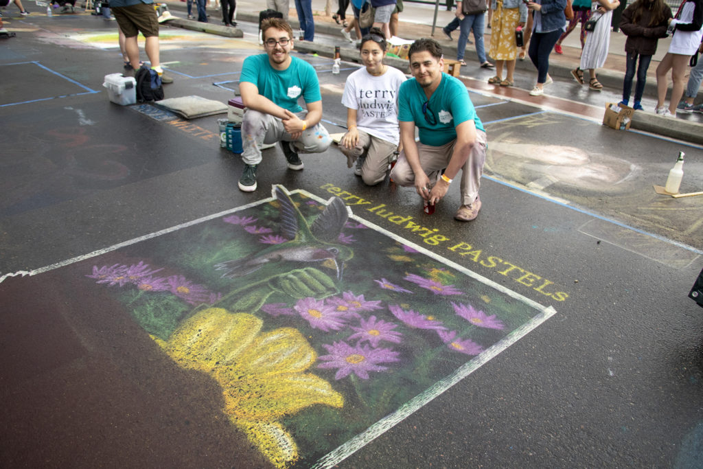 Phillip Bernal (right to left) and his assistants Sheridan Vigil and Brennan Livingston pose with their chalk art which, because of the pastels they used, amazingly survived a sudden downpour. The Denver Chalk Art Festival at Larimer Square, June 1, 2019. (Kevin J. Beaty/Denverite)