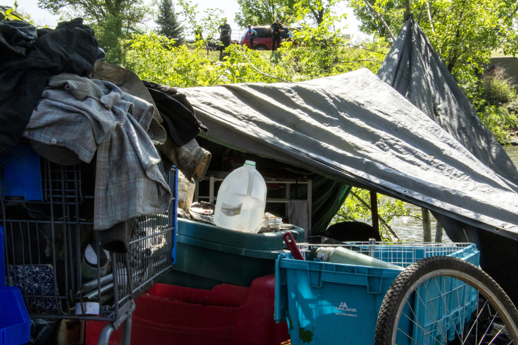 """Police look over John Maki's camp as they """"sweep"""" people living along the South Platte River, June 4, 2019. (Kevin J. Beaty/Denverite)"""
