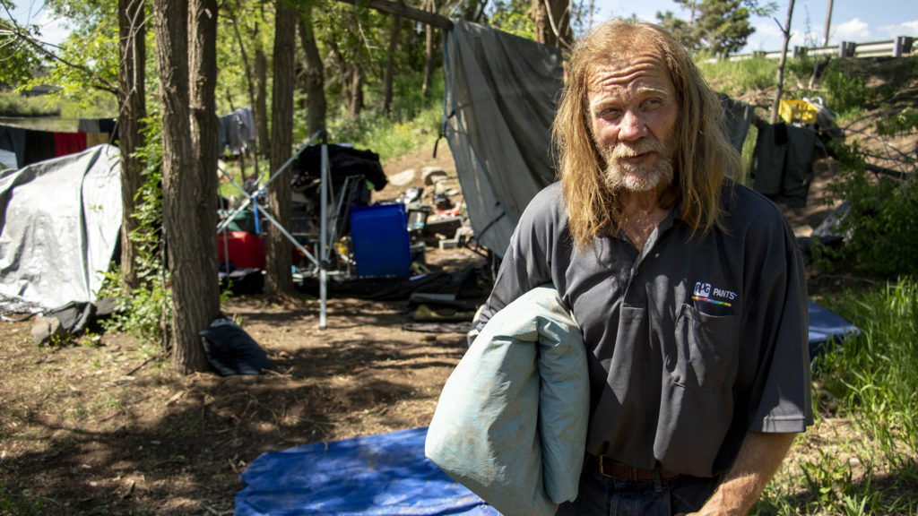 """John Maki cleans up his camp as Englewood and Denver police """"sweep"""" people like him living along the South Platte River, June 4, 2019. (Kevin J. Beaty/Denverite)"""
