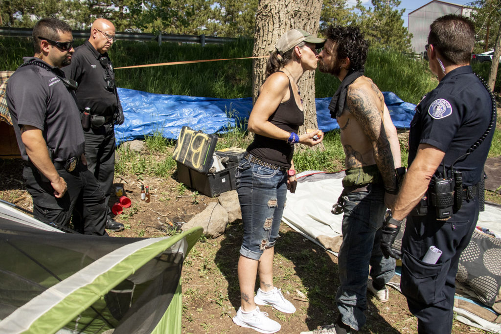 """Brandi Kemp kisses her husband, Derek, as police arrest him during a """"sweep"""" of people living along the South Platte River, June 4, 2019. (Kevin J. Beaty/Denverite)"""