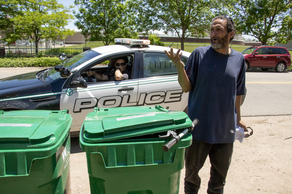 Walt Collins speaks to a reporter along the South Platte as Englewood police officers pull up to check on his clean-up effort. June 5, 2019. (Kevin J. Beaty/Denverite)