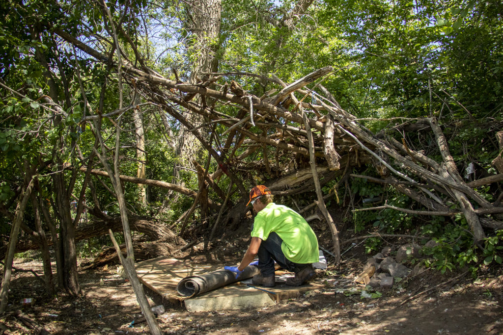 A subcontractor with the city of Englewood cleans up the remains of an encampment along the South Platte River, June 6, 2019. (Kevin J. Beaty/Denverite)