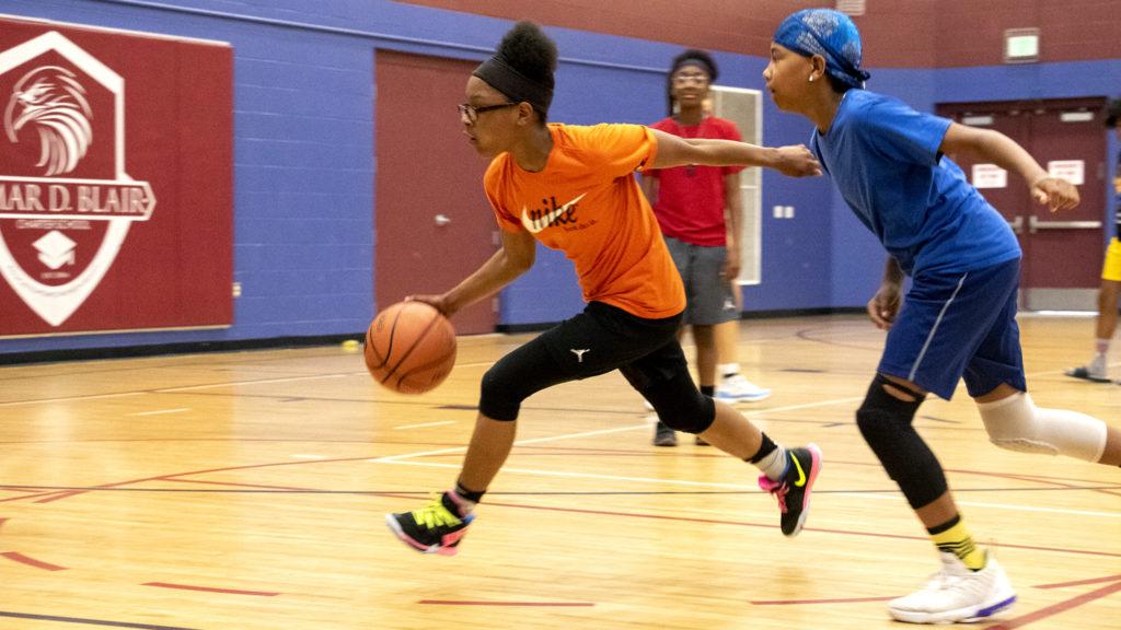 Aniiya (13) makes a drive down a court inside the Green Valley Ranch Recreation Center, June 12, 2019. (Kevin J. Beaty/Denverite)
