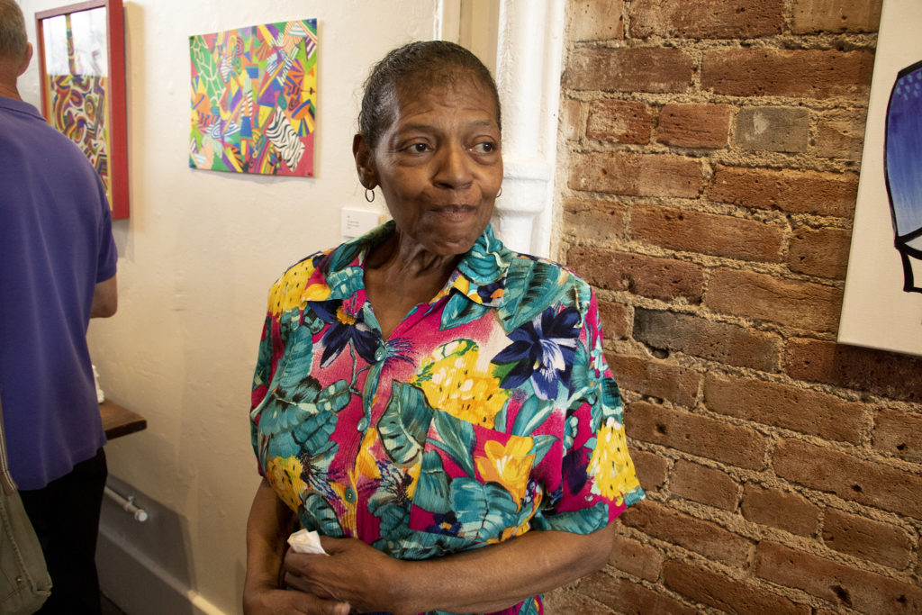 Cynthia Buchanan poses with her work at the Art Restart installation at the Leon Gallery, June 14, 2019. (Kevin J. Beaty/Denverite)