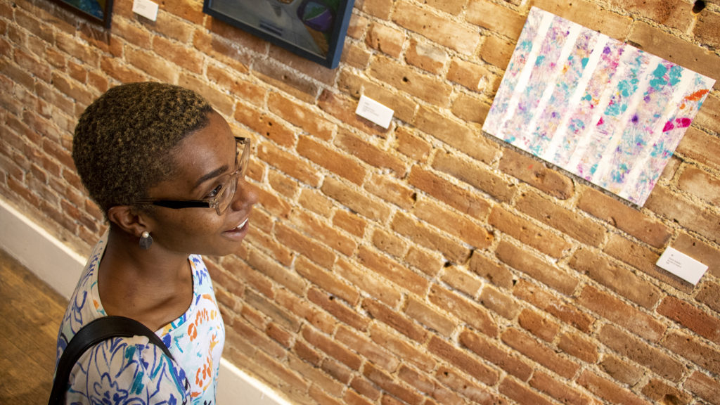 """Kylee Wellons speaks to a reporter about her work hanging in """"Shifting Outlines,"""" a show  featuring artists from The Gathering Place who are being trained by teachers from the Art Students League of Denver, at the Leon Gallery, June 14, 2019. (Kevin J. Beaty/Denverite)"""