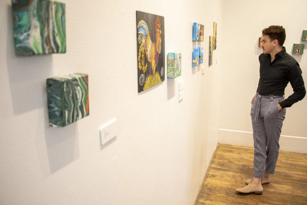 Marlo Olivas chacks out the Art Restart installation at the Leon Gallery, June 14, 2019. (Kevin J. Beaty/Denverite)