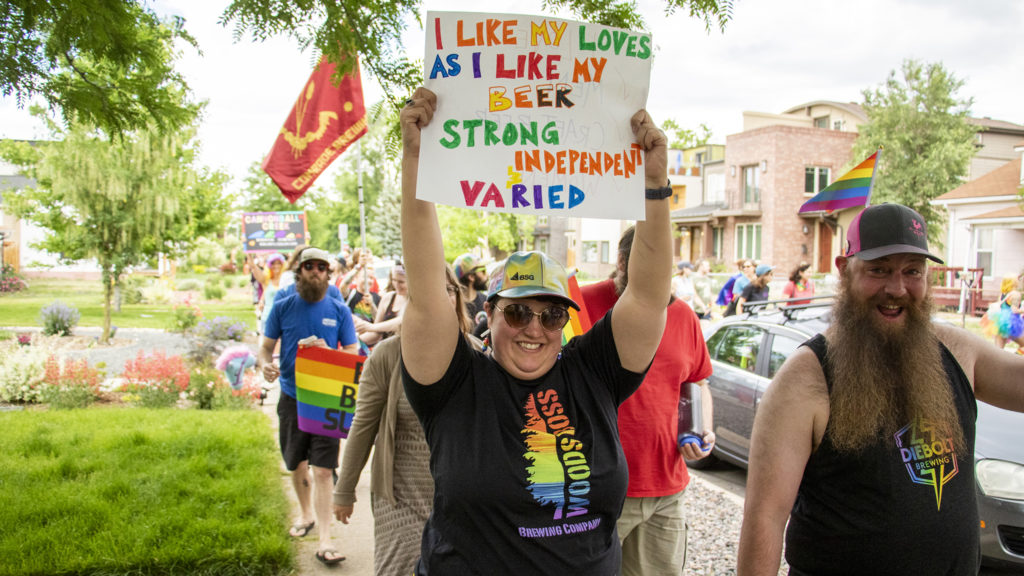 """A marcher holds a sign reading, """"I like my loves like I like my beer,"""" during a craft beer Pride parade in Berkeley, June 15, 2019. (Kevin J. Beaty/Denverite)"""