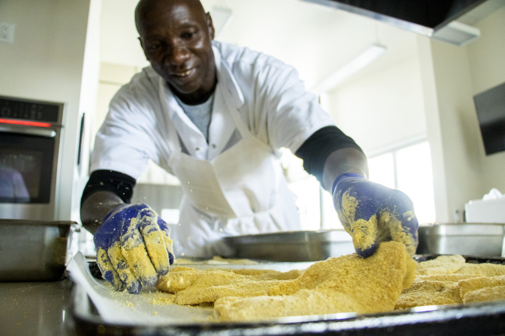 2 Succeed culinary program participant Edward Ray Simmons preps catfish for a fish fry at the Dahlia Campus for Health and Well-Being, June 19, 2019. (Kevin J. Beaty/Denverite)