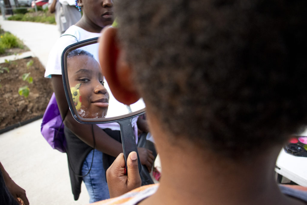 Brian (11) checks out the Pikachu art freshly painted on his face during the Dahlia Campus for Health and Well-Being's annual fish fry, June 19, 2019. (Kevin J. Beaty/Denverite)