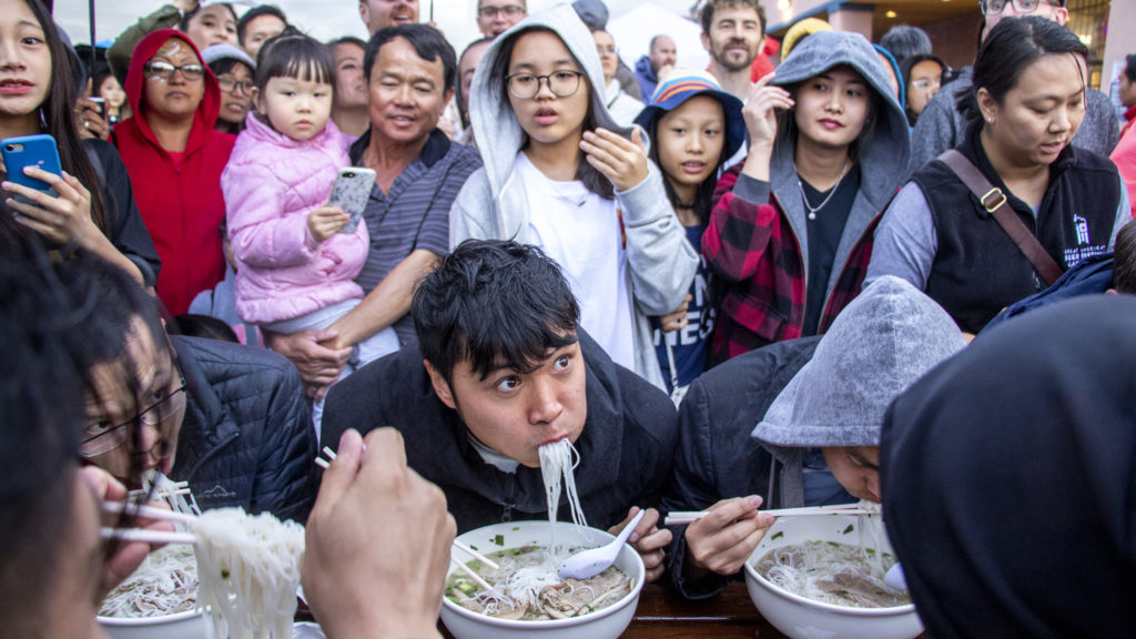 Jack Le struggles to keep up during a pho eating context at the Little Saigon Night Market. Federal Boulevard, June 21, 2019. (Kevin J. Beaty/Denverite)