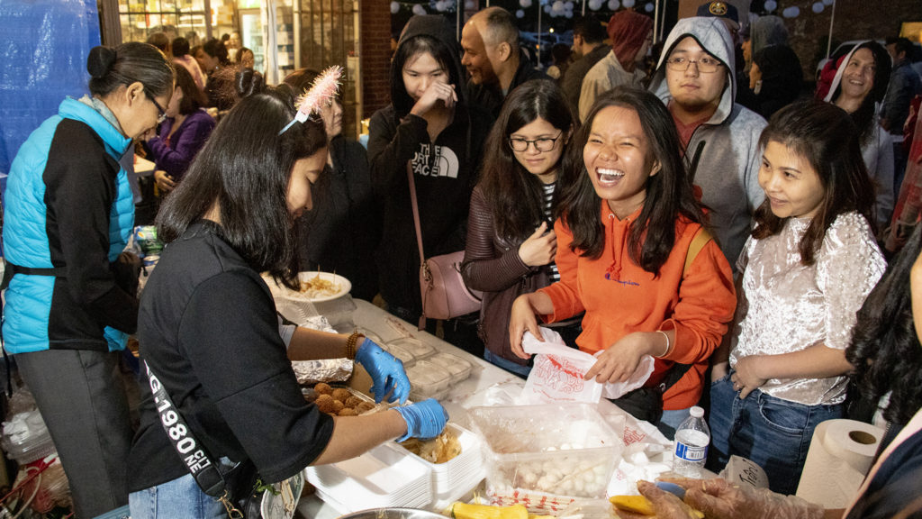 Customers line up for snacks at Troung An Gift's tent at the Little Saigon Night Market along Federal Boulevard, June 21, 2019. (Kevin J. Beaty/Denverite)