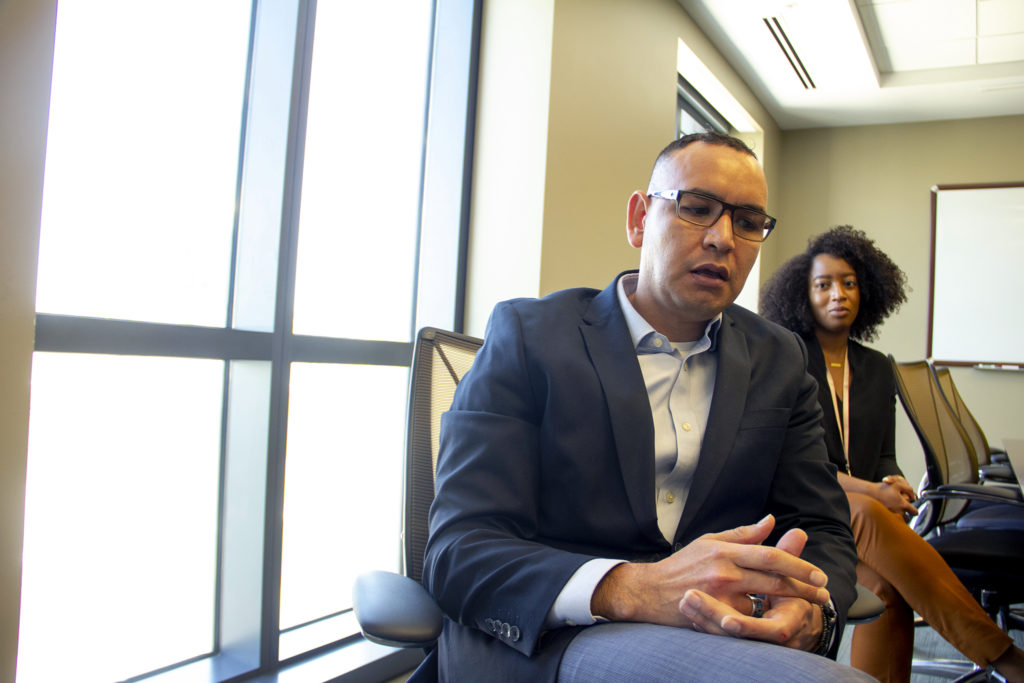 Efrain Buenos, an administrator at the Colorado Attorney General's office, speaks to a reporter. July 9, 2019. (Esteban L. Hernandez/Denverite)