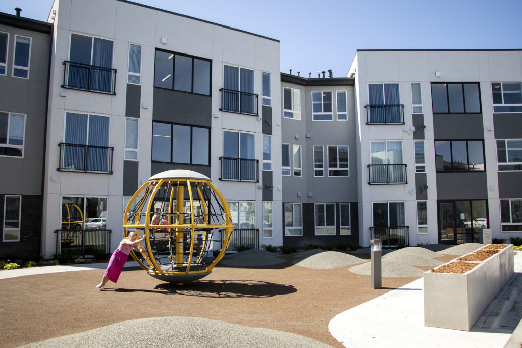 Kids play on a playground outside the Moline Apartments in Stapleton, July 19, 2019. (Kevin J. Beaty/Denverite)
