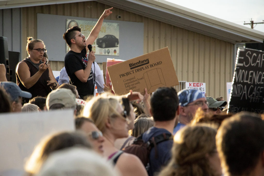 Cristian Solano-Córdova addresses protesters gathered outside of Aurora's private immigration detention facility to denounce ICE raids and jails like this across the country, June 14, 2019. (Kevin J. Beaty/Denverite)