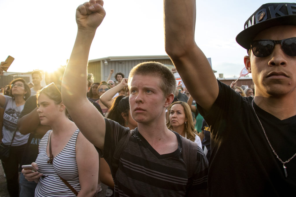 Tyrone Newsom (from right) and Theo Spain hold up fists as protesters gatheref outside of Aurora's private immigration detention facility, June 14, 2019. (Kevin J. Beaty/Denverite)