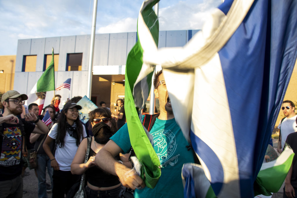 A protester who asked not to be named rips apart a flag with GEO's logo on it, the contractor operating Aurora's private immigration detention facility, June 14, 2019. (Kevin J. Beaty/Denverite)