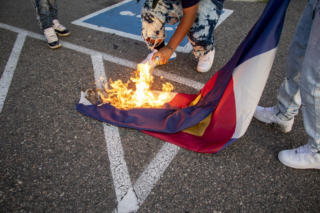 Protesters burn a Colorado state flag on federal property outside of Aurora's private immigration detention facility, June 14, 2019. (Kevin J. Beaty/Denverite)