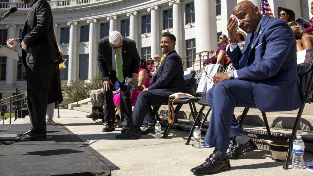 Mayor Michael Hancock wipes his forehead on a hot inauguration day on the City and County Building steps, July 15, 2019. (Kevin J. Beaty/Denverite)