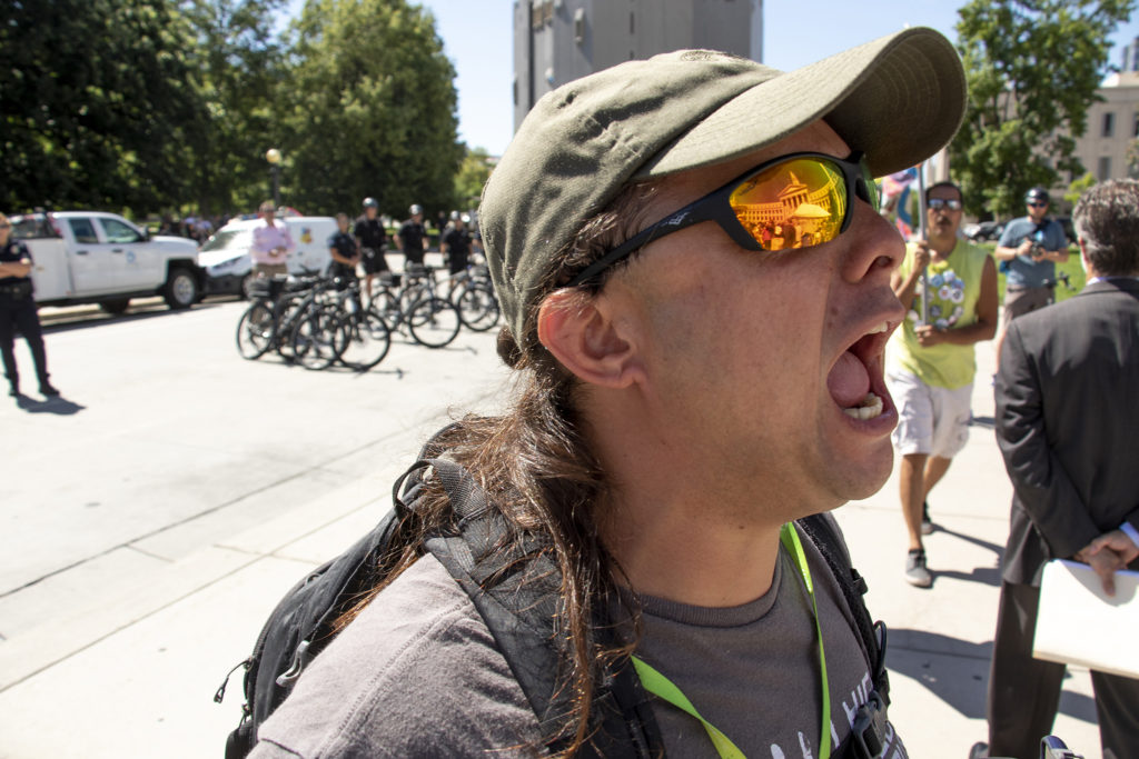 Brian Loma yells protests during Mayor Michael Hancock's inauguration day speech in front of the City and County Building, July 15, 2019. (Kevin J. Beaty/Denverite)