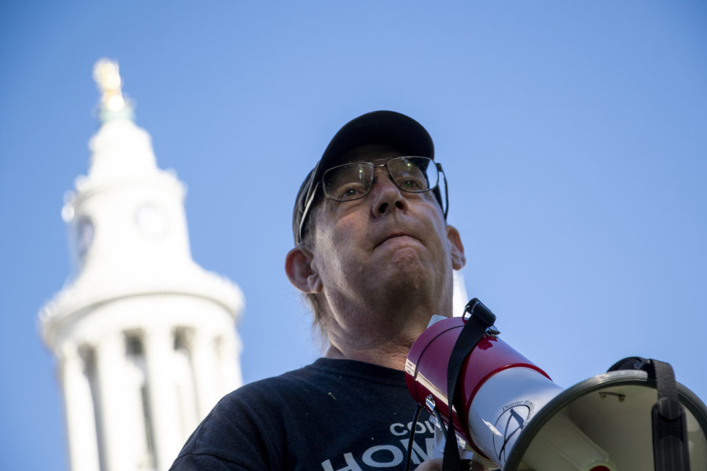 """BenjaminDunning, co-founder of Denver Homeless Out Loud, speaks as his group kicks off """"100 days of dignity"""" with a press conference at Civic Center Park, July 15, 2019. (Kevin J. Beaty/Denverite)"""