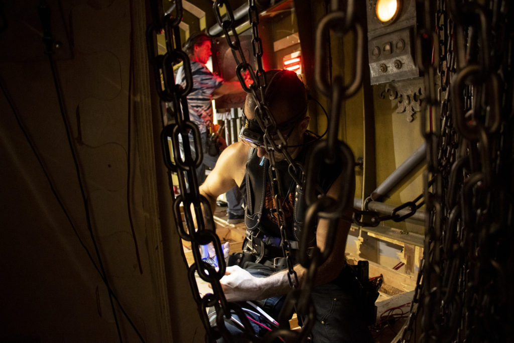 """Matthew Noble, who once built contraptions for TV's """"Mythbusters,"""" tinkers inside a submarine-themed attraction at Urban Putt's new location at the old Old Spaghetti Factory building downtown, July 16, 2019. (Kevin J. Beaty/Denverite)"""
