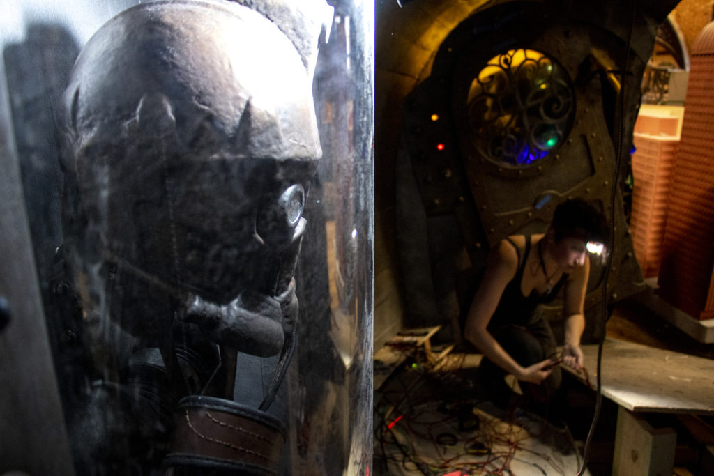 Arianna Feldman works inside a spaceship-themed hole inside Urban Putt's new location at the old Old Spaghetti Factory building downtown, July 16, 2019. (Kevin J. Beaty/Denverite)