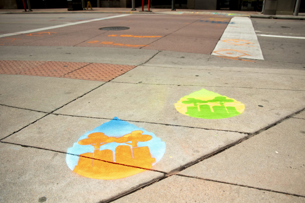 Sidewalk paintings by artist Pat Milbery at 14th and Curtis Streets promoting Denver Parks and Recreation's downtown tree canopy expansion, July 17, 2019. (Kevin J. Beaty/Denverite)