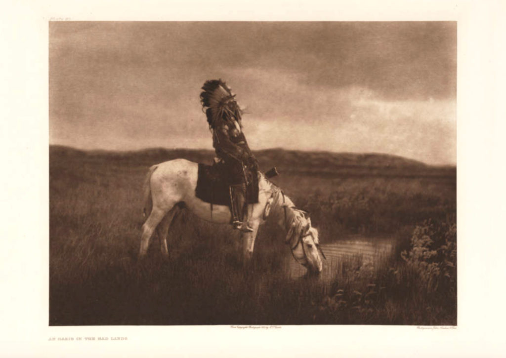 Red Hawk (Chetan-luta), a Native American (Oglala Sioux) man, sits on horseback at a watering hole in the Badlands in South Dakota. Circa 1905. (Denver Public Library/Western History Collection/X-34083)