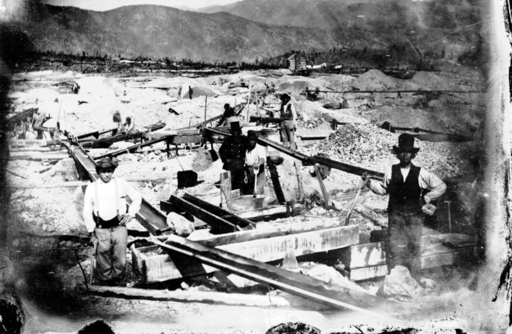 A group of miners pose, with shovels and pans, by a system of wooden sluices in Gilpin County, Colorado, Circa 1865. (Rufus E. Cable/Denver Public Library/Western History Collection/X-61762)