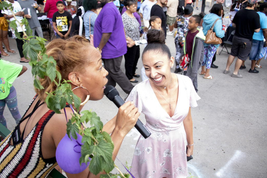 Danette Hollowell sings to greet City Councilwoman Candi CdeBaca as she arrives to Welton Street Cafe's 20th anniversary celebration in one location. Five Points, July 30, 2019. (Kevin J. Beaty/Denverite)