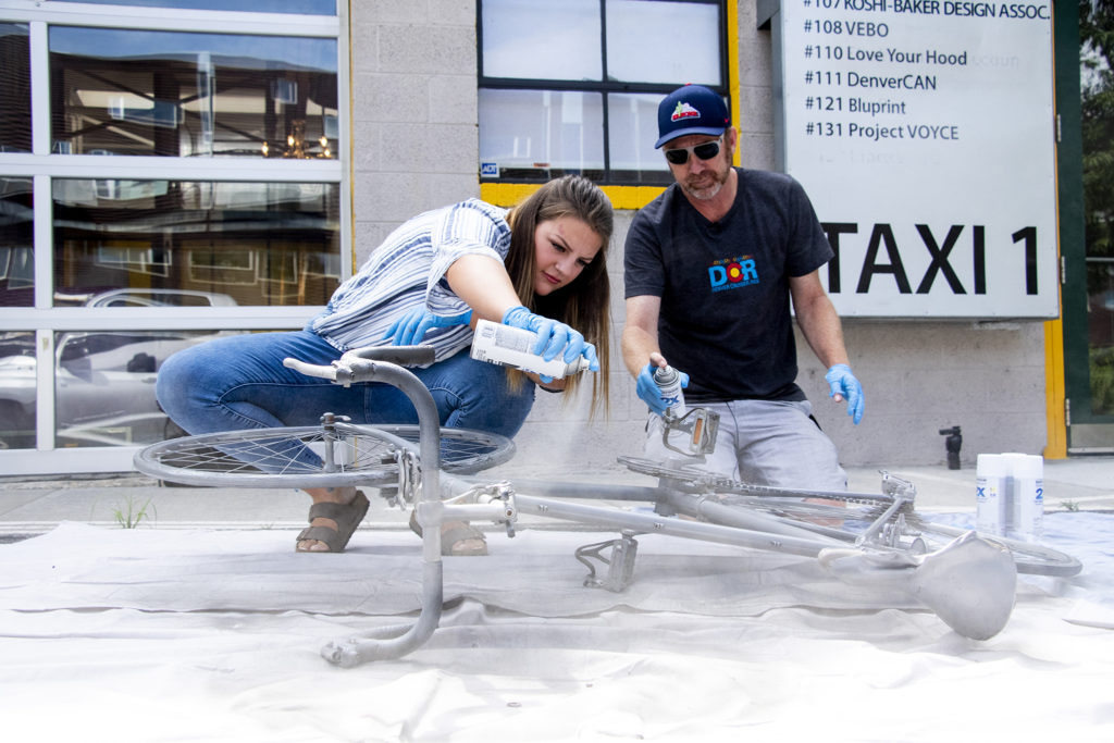 """Madison Hendrickson and Brad Evans paint a """"ghost bike"""" in honor of Hendrickson's father, Scott, who was killed while riding his bike. Taxi campus, July 30, 2019. (Kevin J. Beaty/Denverite)"""
