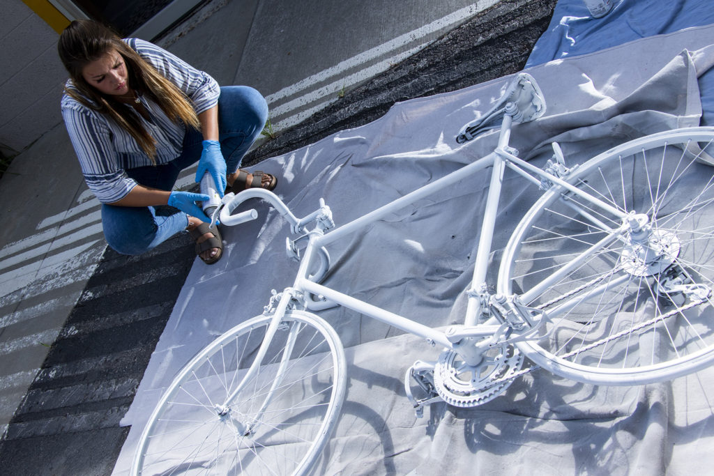 "Madison Hendrickson paints a ""ghost bike"" in honor of her father, Scott, who was killed while riding his bike. Taxi campus, July 30, 2019. (Kevin J. Beaty/Denverite)"