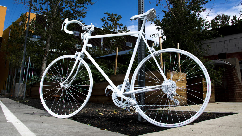 """The """"ghost bike"""" Madison Hendrickson and Brad Evans painted in honor of Hendrickson's father, Scott, who was killed while riding his bike. Taxi campus, July 30, 2019. (Kevin J. Beaty/Denverite)"""