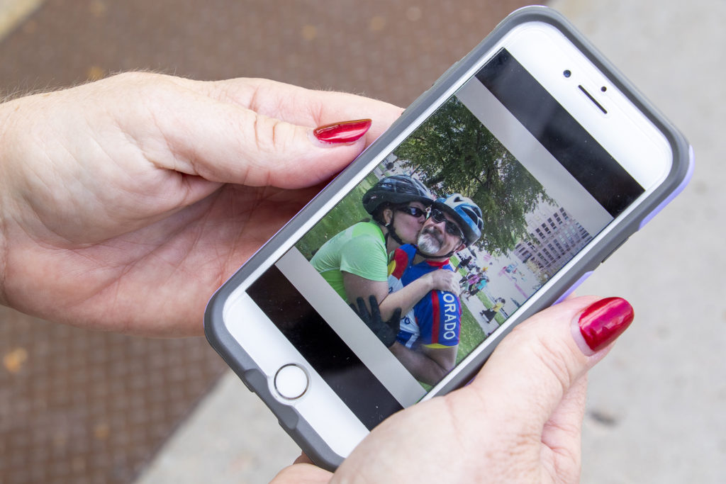 Shelly Kaveney Hendrickson pulls up a photo of herself with her late husband, Scott, who was killed while riding his bike. Taxi campus, July 30, 2019. (Kevin J. Beaty/Denverite)