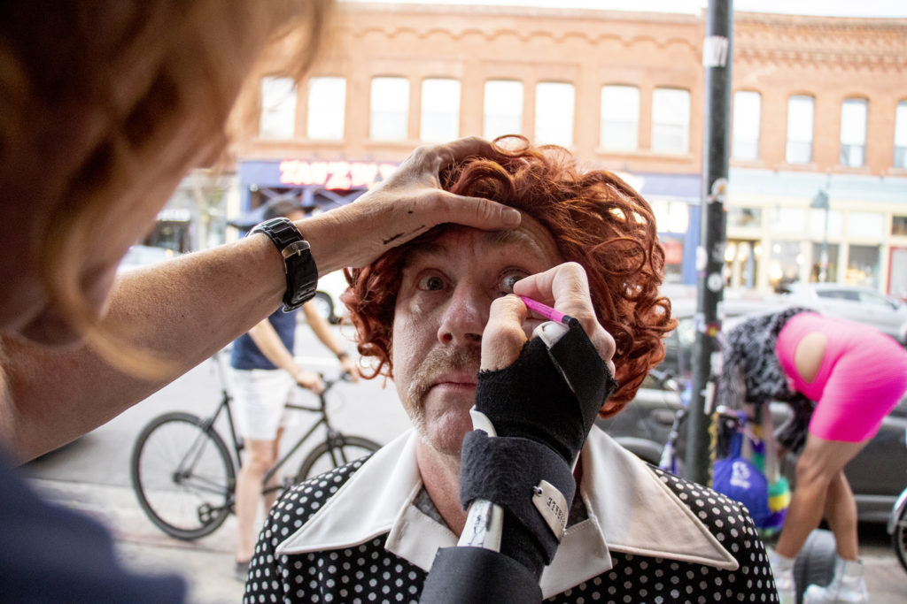 Brad Evans gets makeup on his face before the Denver Cruiser Ride on July 31, 2019. (Kevin J. Beaty/Denverite)