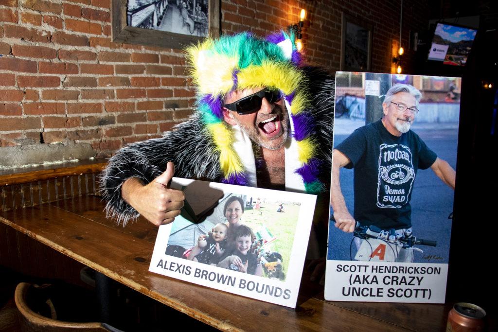 Darren Droge poses with photos of Scott Hendrickson before the Denver Cruiser Ride on July 31, 2019. (Kevin J. Beaty/Denverite)
