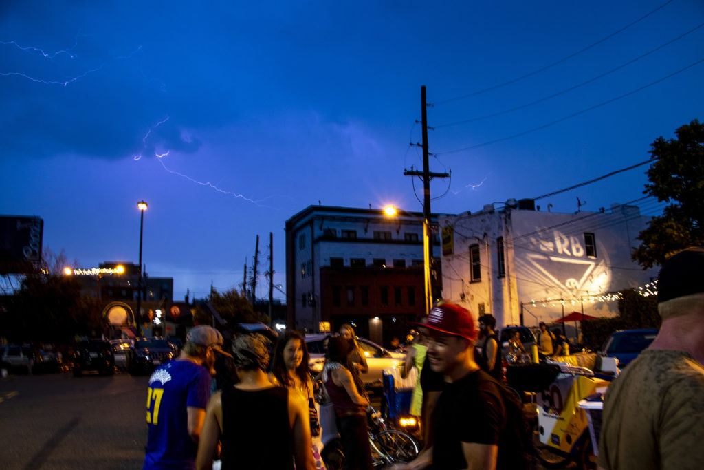Lightning strikes over people hang out in the parking lot behind The Gin Mill before the Denver Cruiser Ride on July 31, 2019. (Kevin J. Beaty/Denverite)