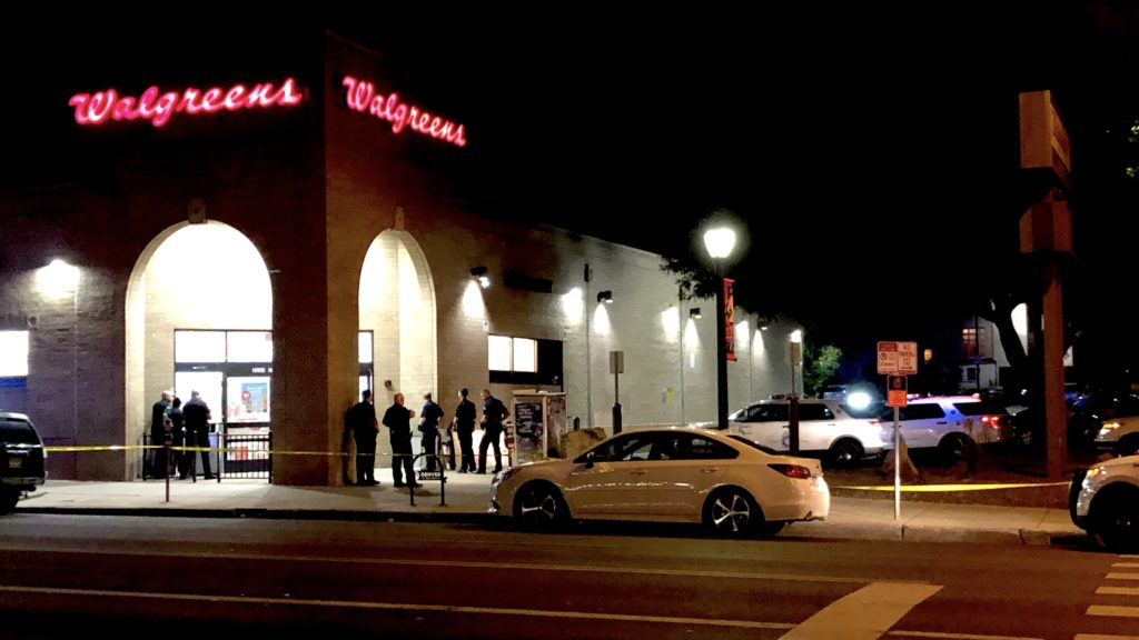 A group of police officers attempt to coax a suspect out of the Walgreens on East Colfax Avenue. (David Sachs/Denverite)