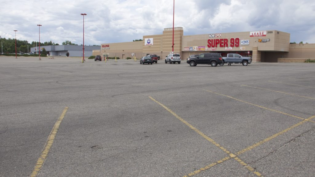 A mostly empty parking lot at the Super 99 Cents store on South Sheridan Boulevard on Monday, July 8, 2019, in Denver. (Esteban L. Hernandez/Denverite)