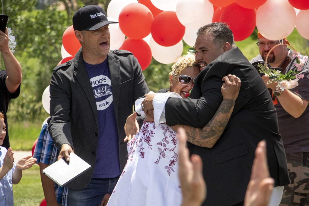 "Bryan ""Pastor B"" Sederwall officiates Carlos and LaShawn Serrat's wedding during the Denver Dream Center's Father's Day barbecue at City of Cuernavaca Park, June 15, 2019. (Kevin J. Beaty/Denverite)"