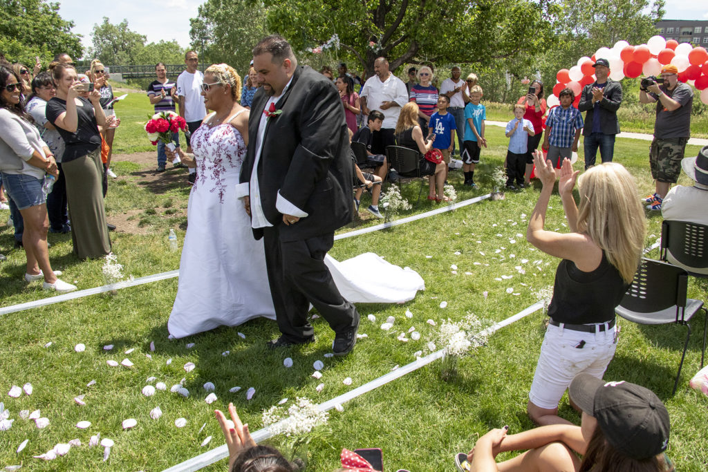 Carlos and LaShawn Serrat walk down the aisle after their wedding during the Denver Dream Center's Father's Day barbecue at City of Cuernavaca Park, June 15, 2019. (Kevin J. Beaty/Denverite)