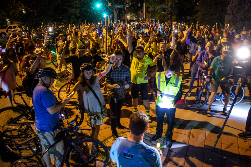 Father Joseph Dang leads the audience into a moment of silence during a vigil for Alexis Bounds on the block where she died on her bike. July 31, 2019. (Kevin J. Beaty/Denverite)