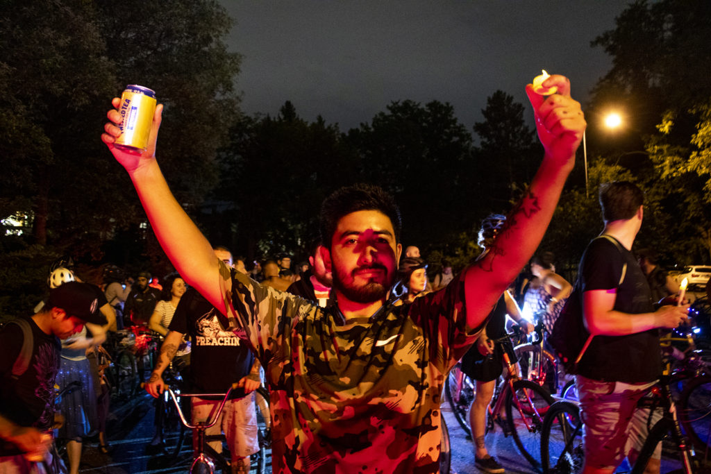 Vince Quinones holds up a can and a candle during a vigil for Alexis Bounds on the block where she died. July 31, 2019. (Kevin J. Beaty/Denverite)