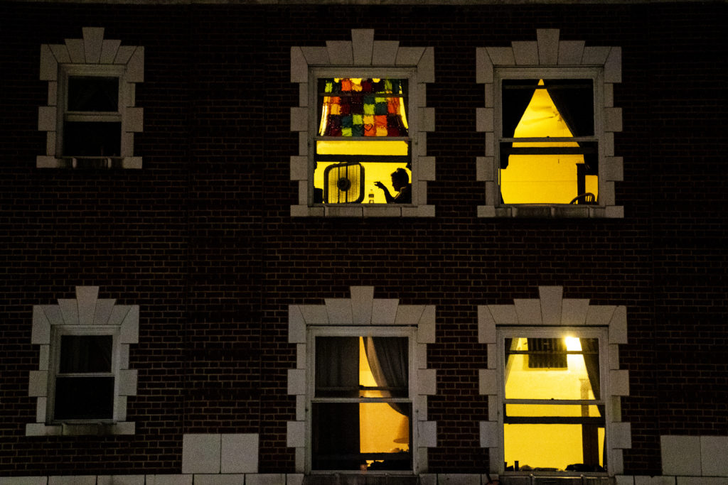 Someone hangs out near a fan and a window on a hot summer night inside the Newhouse Hotel on West Colfax Avenue, Aug. 4, 2019. (Kevin J. Beaty/Denverite)