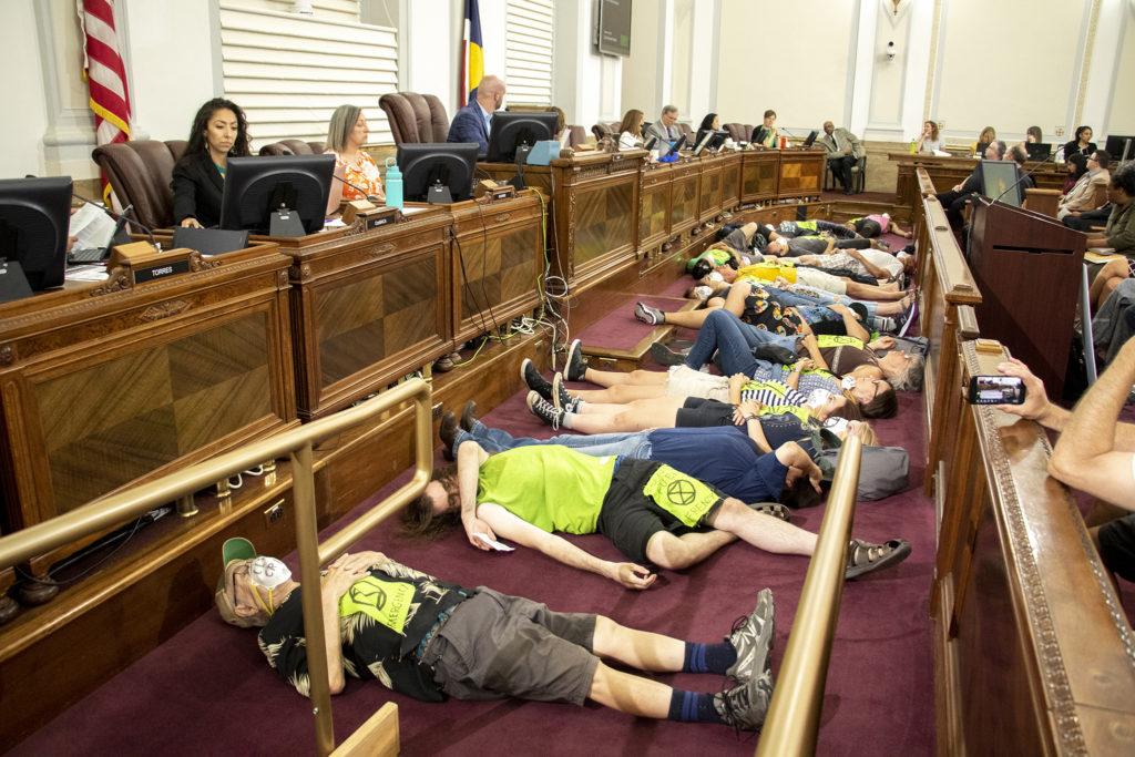 "Climate change activists perform a ""die-in"" during Denver City Council. Aug. 5, 2019. (Kevin J. Beaty/Denverite)"
